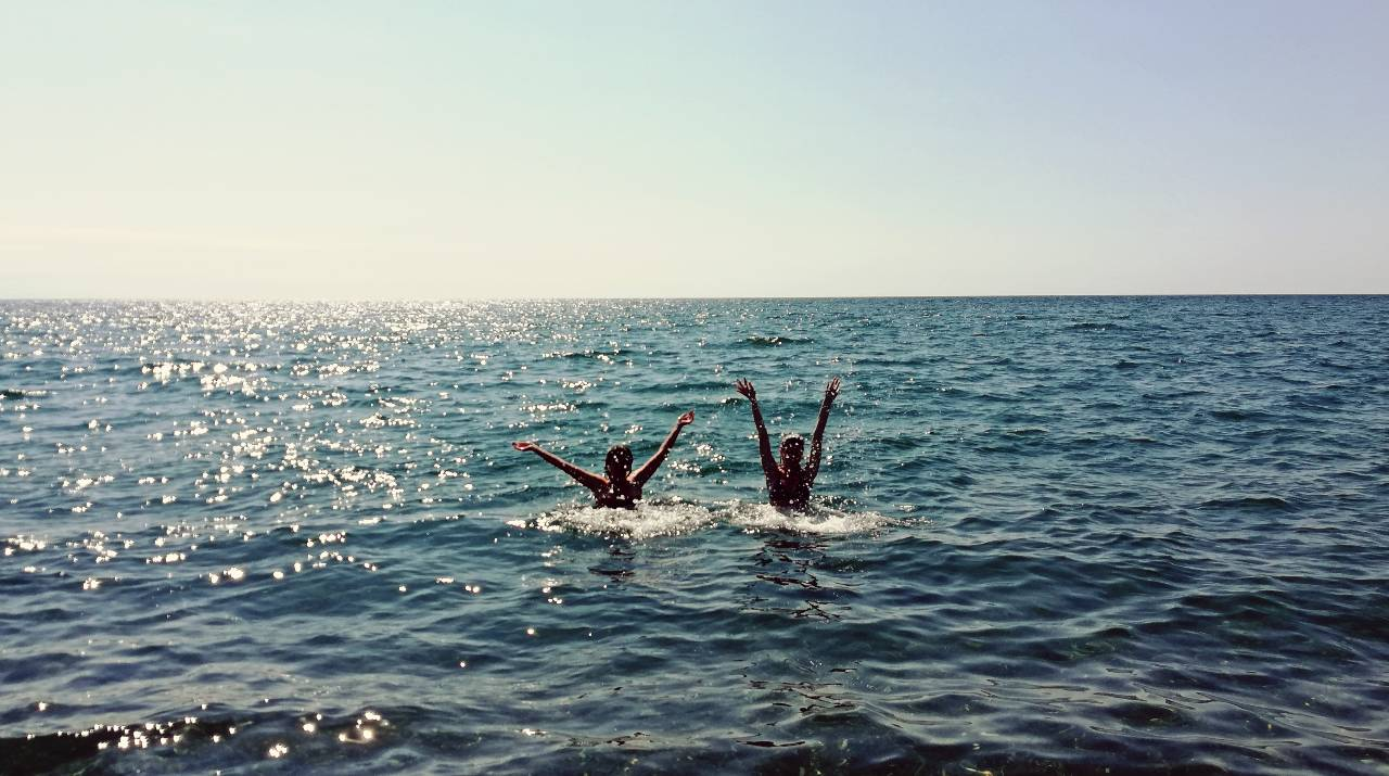Two women happily playing and swimming in the ocean